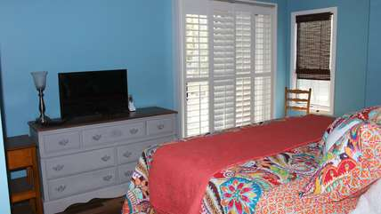 The master bedroom has a king bed and doors leading to a small deck.