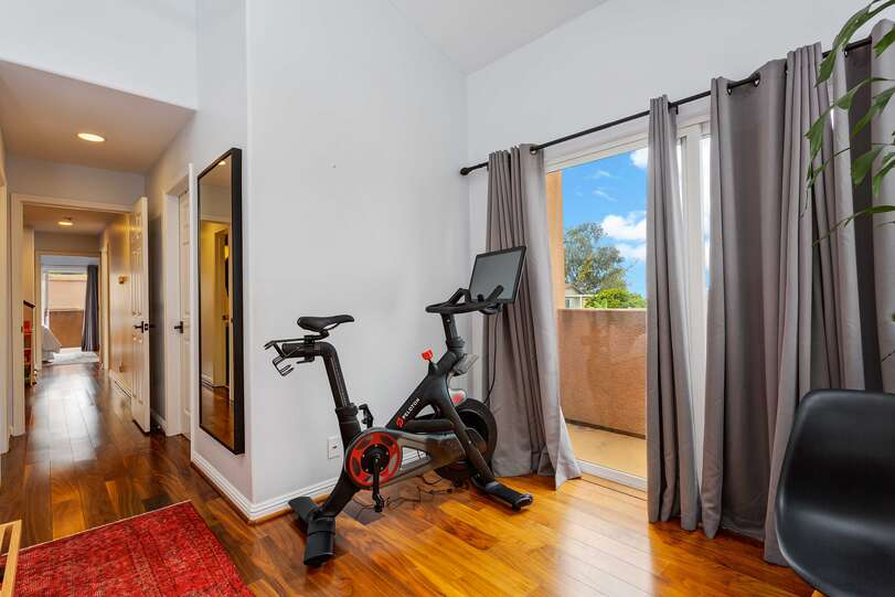 An exercise area opposite the bed rewards with an ocean view and balcony