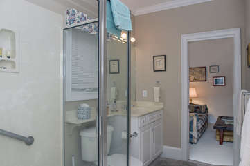 The bath off the den has a sink, shower, and toilet that are connected to the master bath by a pocket door.