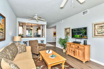 Living Room with Flat Screen TV, Fan, and Entrance to Lanai Area with Lake and Golf Views; Couch is a Pull Out!