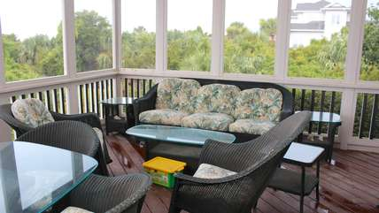 Step to the screened porch and relax on the cushioned wicker furniture.