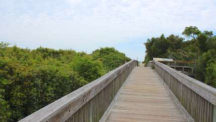 Walk down the boardwalk to sit on the beach.