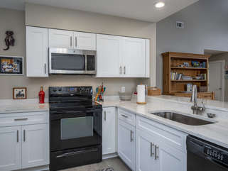 The open kitchen is equipped with what you'll need to cook.