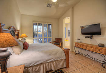 Master bedroom has king bed, large TV and view of outdoors