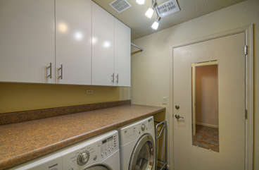 Completely stocked laundry room with family size appliances and space to manage laundry tasks