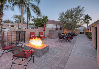 Patio is furnished for relaxing around fire pit and dining outdoors