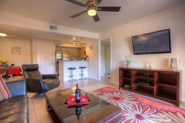 Living room is arranged for watching large flat screen TV or relaxing with favorite drink and good book