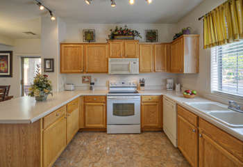 Kitchen has custom cabinets and lots of counter space for serving food and beverages