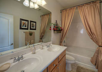 Master bath features double vanity sinks and tub/shower combination