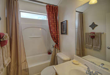 Upstairs bath features tub/shower combination with transom window