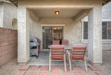 Covered patio has comfortable dining furniture and a barbecue for grilling