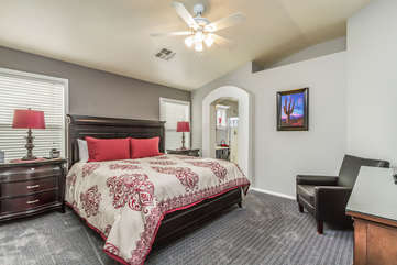 Well appointed master bedroom with king bed and walk-in closet is at back of home