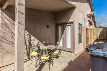 Private covered patio has grill and dining furniture for outdoor cooking and eating