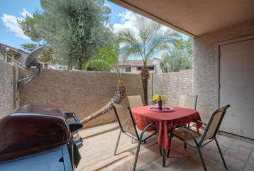 Covered patio is furnished for outdoor dining and barbecuing foods