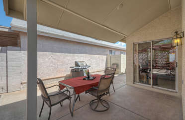 Covered patio with dining furniture and gas grill for those who love dining in the great outdoors
