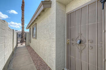 Gated side entrance to front door of one story NE Mesa home
