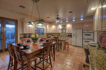 Designer kitchen has table and bar seating, and bright open spaces for entertaining guests
