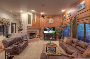 Crowd pleasing features of living room include comfortable seating that reclines to enjoy large TV and charming gas fireplace