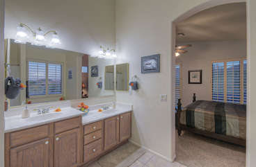Master bath features dual vanity sinks and enclosed commode
