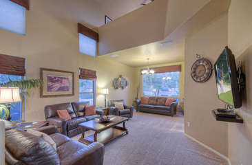 Large great room with backyard view has TV for entertainment and pool view.