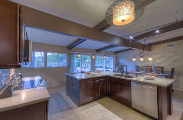 Workspace in kitchen is well lit and designed to be efficient for preparing and serving delectable cuisine.