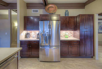 Designer kitchen boasts granite counters, stainless steel appliances and beautiful tile floors