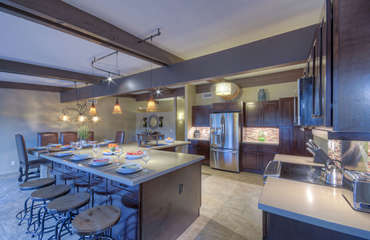 Exquisite designer kitchen is well stocked with everything you need to concoct your favorite meals and beverages and has large island for bar seating
