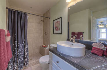 Beautifully remodeled walk-in shower and vessel sink are appealing features of master bath