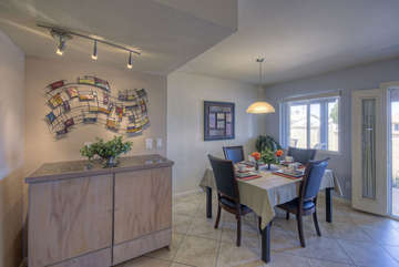Dining area is bright and cheerful with track lights, large windows and door to enclosed backyard