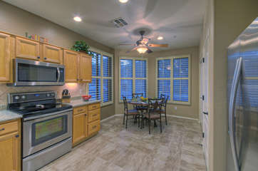 Kitchen opens into breakfast nook with table seating for 4 and enticing outdoor views from large windows