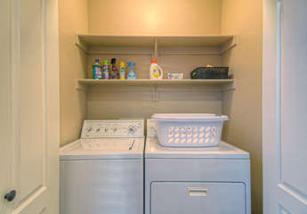 Behind double doors and off kitchen is fully stocked laundry room