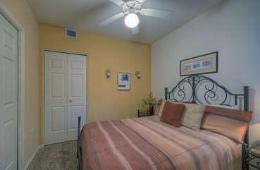 Warm and cozy second bedroom has queen bed and ceiling fan