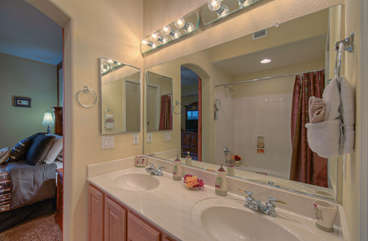 Master bath features dual vanity sinks and tub/shower combination