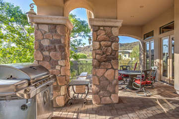 Covered porch with gas grill, television and variety of seating arrangements runs length of home