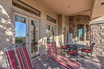 Loungers, dining furniture and TV offer shaded interlude on expansive back porch