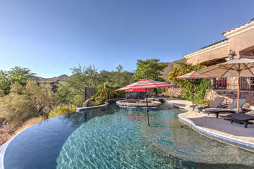 Divine infinity edge pool with option to heat has swim-up bar and fountain