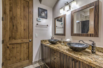 Safari theme continued in bath which features two stylish vessel sinks