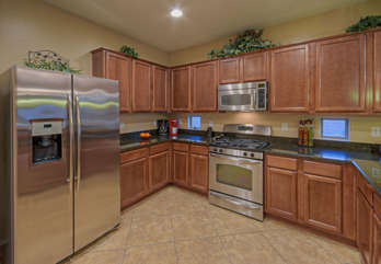 Kitchen features custom cabinets, granite counters and stainless steel appliances