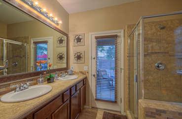 Master suite bath has dual vanity sinks and door to back patio