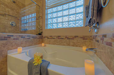 Glass walk-in shower and divine garden tub are appealing features of master bath