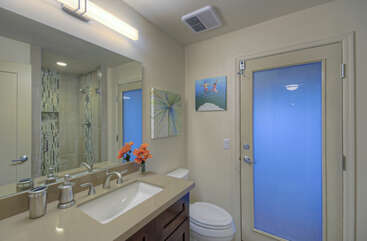 Fourth bedroom and adjacent futon room share third bathroom with a walk-in shower and access to back patio