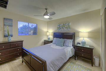 Pretty third bedroom has a queen bed, ceiling fan and TV