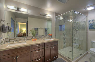 Ensuite primary bath has dual vanity sinks and a large walk-in glass shower