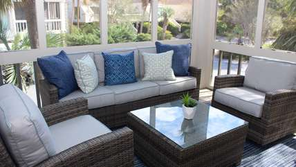 The screened porch has comfortable, upholstered wicker furnishings.