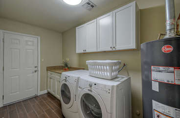 Separate laundry room is equipped with new washer and dryer
