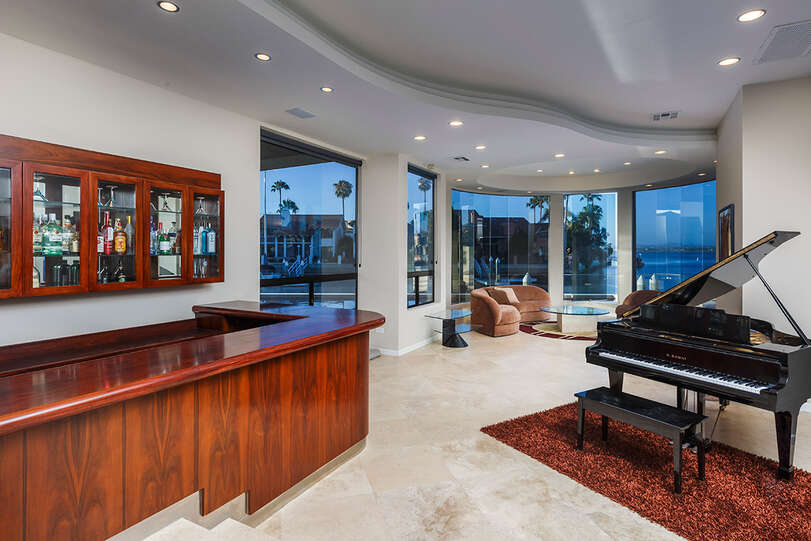 A piano, full wet bar, and conversation lounge are part of the large living room