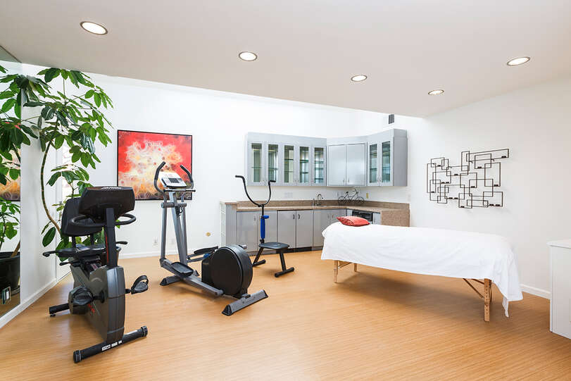 The gym has a variety of equipment, a massage table, and can double as a bedroom if needed