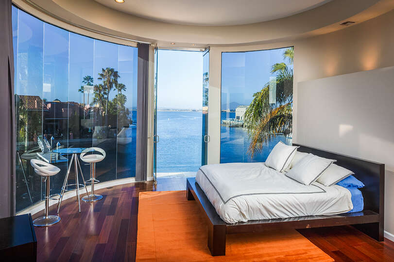 Bedroom 4 features an amazing curved glass wall to capitalize on gorgeous views