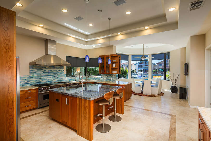 Stylish beach inspired kitchen includes a huge gas range, double ovens, dishwashers, and several dining areas