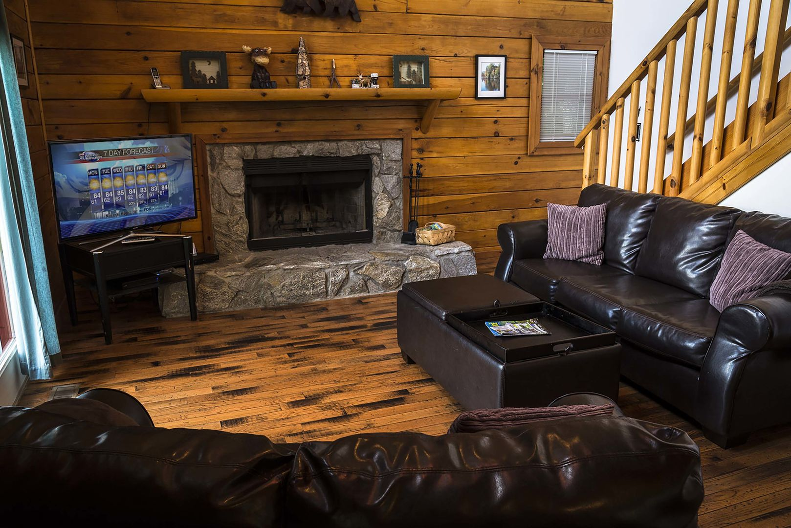 Living room with HDTV and stone wood burning fireplace